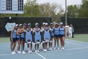 From left to right, seniors Marika Akkerman, Maggie Kane and Cassandra Vazquez pose with their team on Senior Sunday against Pittsburgh on April 22 at the Cone-Kenfield Tennis Center.
