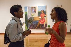Christina Perkins (left) talks with artist Mequitta Ahuja (right) about her artwork during her exhibit, Meaningful Fiction and the Figurative Tradition, in the Sonja Haynes Stone Center for Black Culture and History on Thursday evening.