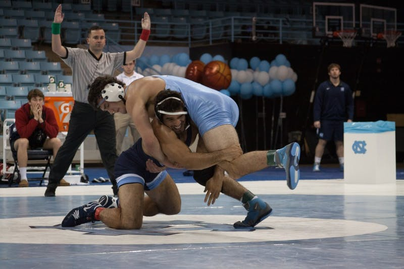 Redshirt senior Ethan Ramos (in Navy) goes for the legs of sophomore teammate Devin Kane during UNC's wrestle-offs on Friday night in Carmichael Arena.