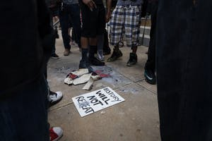"""A sign that reads """"History will not repeat"""" lies next to the burnt remains of a Confederate flag."""