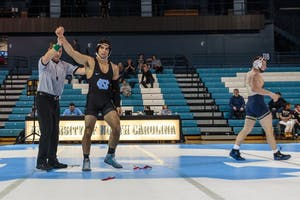 UNC's Ethan Ramos celebrates after winning in the 174-pound bout during the team's match against Pittsburgh on Jan. 26 in Carmichael Arena.