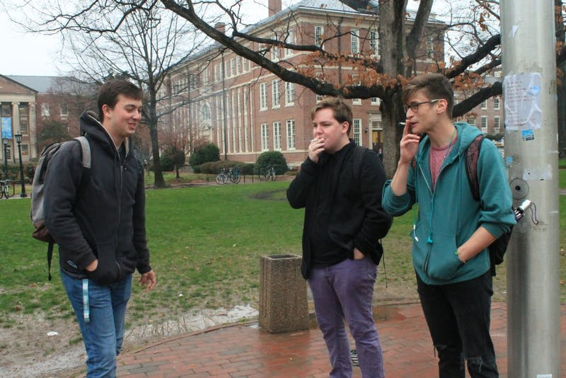 From left to right: UNC students Ethan Gilbreath, James Collette and Rory McFarlane smoke by the flagpole in Polk Place on Thursday afternoon.