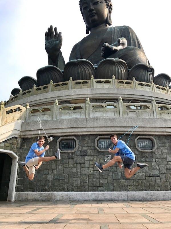 "Noah Mancuso (left) and Graham Booth (right) jump in front of the Tian Tan ""Big Buddha"" in Hong Kong."