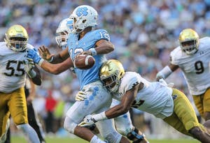 Quarterback Chazz Surratt (12)  is pressured by Notre Dame defenders on Oct. 7 in Kenan Memorial Stadium.