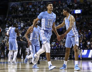 Cameron Johnson (13) gets a high five from Garrison Brooks (15) while running off the court against Duke during the ACC semifinals on March 9 in Brooklyn. Photo courtesy of David Welker, theACC.com