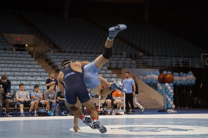 Redshirt senior Ethan Ramos (in Navy) takes down sophomore teammate Devin Kane during UNC's wrestle-offs on Friday night in Carmichael Arena.