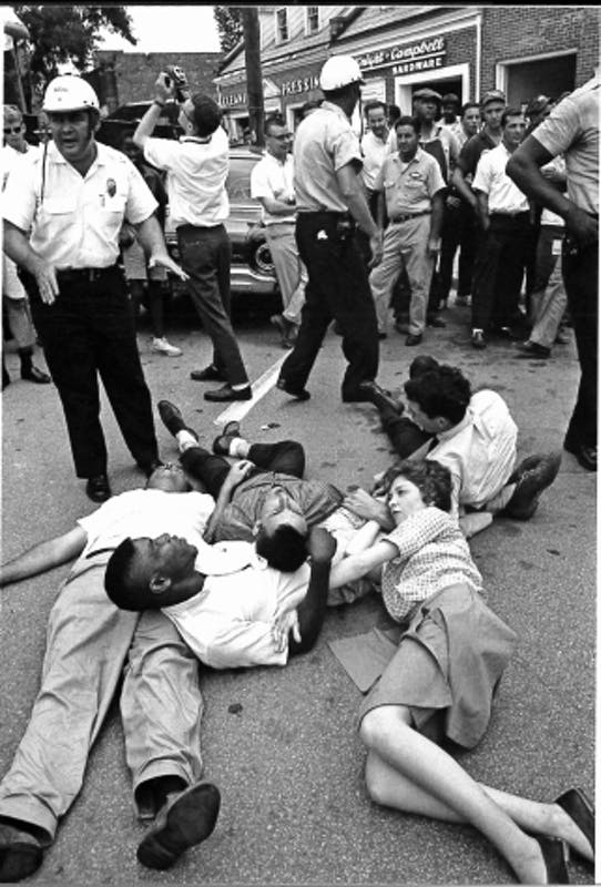 "Photo courtesy of Chapel Hill Public Library, from their book ""Courage in the Moment. The Civil Rights Struggle 1961-1964"" photographed by Jim Wallace. Protestors had to agree to practice nonviolent resistance by neither assisting or resisting arrest, here the demonstrators are lying on Franklin Street, according to the book."