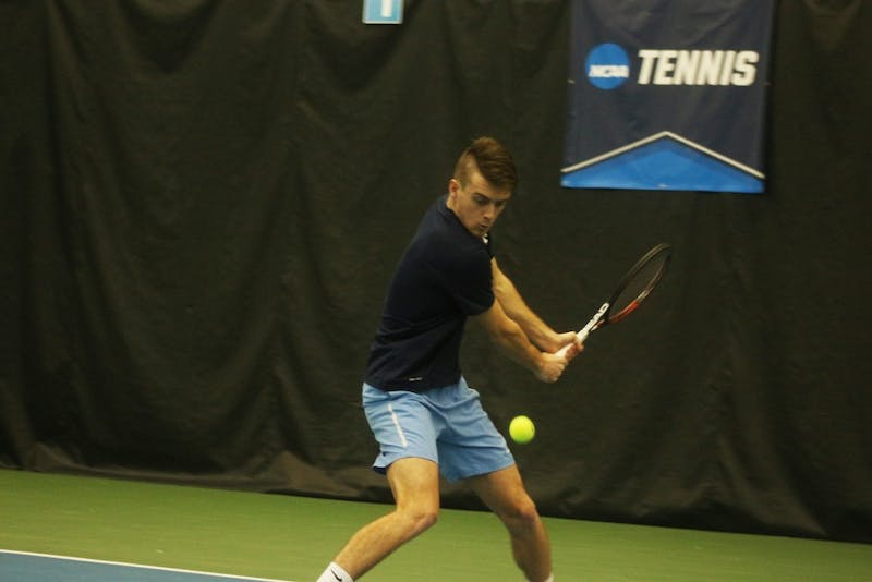 Senior Robert Kelly focuses his backhand in the doubles match against Wofford on Saturday at the Cone-Kenfield Tennis Center.