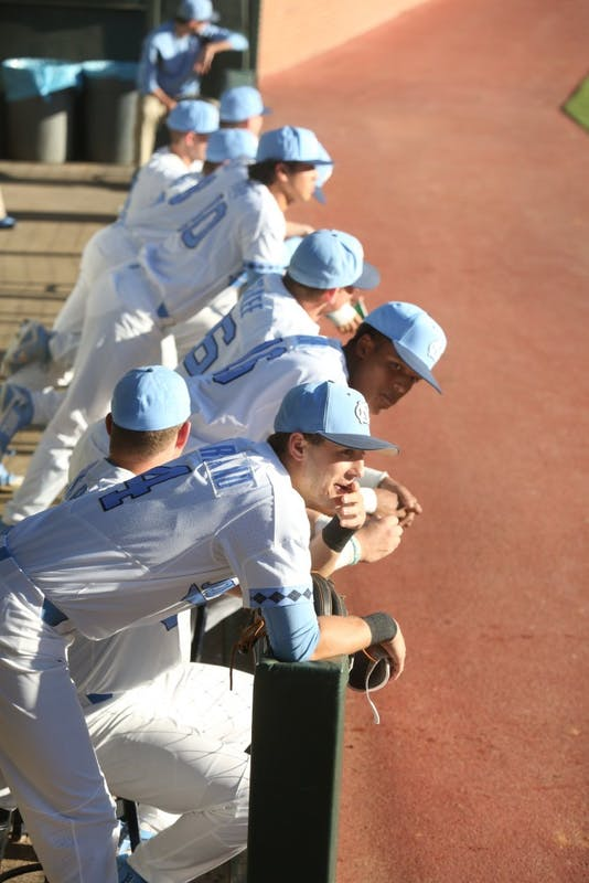 UNC baseball players watch the game against High Point University from the dugout on Feb. 27.