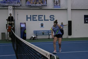 Junior Jessie Aney takes a backhand against Michigan on Feb. 18 in the Cone-Kenfield Tennis Center.