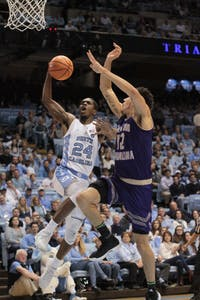 North Carolina guard Kenny Williams (24) goes up for a contested layup over Western Carolina defender Marc Gosselin (12) on Dec. 6 in the Smith Center.