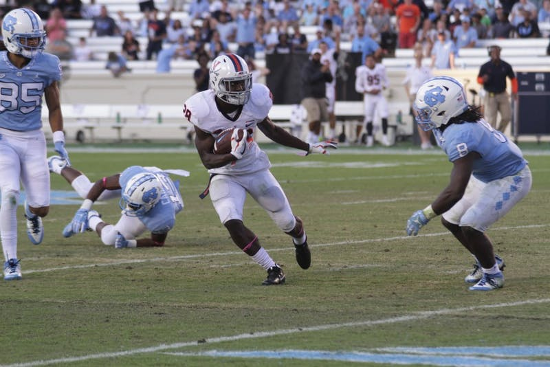 Virginia free safety Brenton Nelson (28) dodges UNC tailback Michael Carter (8) after intercepting the ball on Saturday.