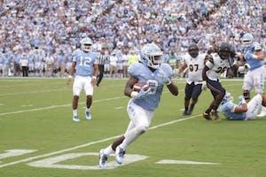 Running back Michael Carter (8) carries the ball against California on Sept. 2.