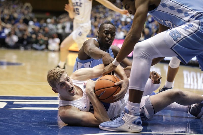 North Carolina wing Theo Pinson (1) and Duke forward Jack White (41) fight for a loose ball on March 3 in Cameron Indoor Stadium.