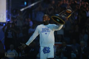 Theo Pinson presents the 2017 national championship trophy at Late Night With Roy on Friday night.