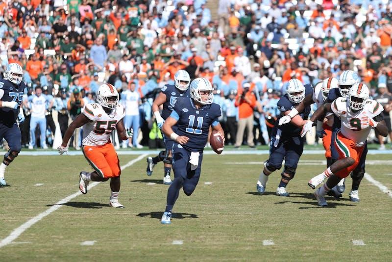 Quarterback Nathan Elliott (11) scrambles against Miami on Oct. 28 in Kenan Stadium.