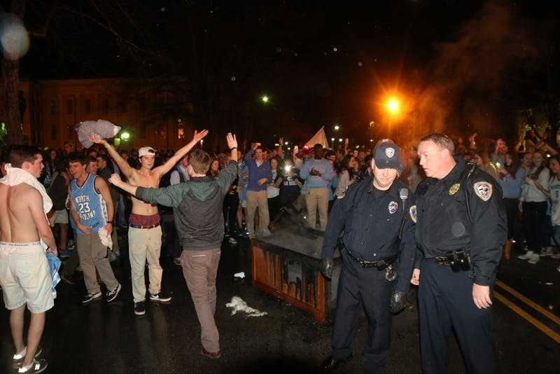 Law enforcement officers put out bonfires on Franklin Street after North Carolina's 76-72 victory over Duke on March 5, 2016.