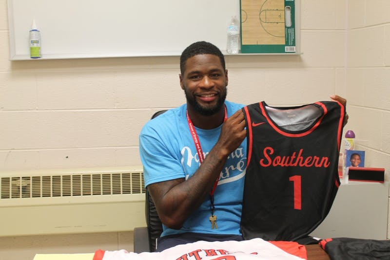 Southern Durham men's basketball head coach David Noel poses with a team jersey. Noel, who won a national championship with the UNC basketball team in 2005, returned to his former high school as a coach in late August.