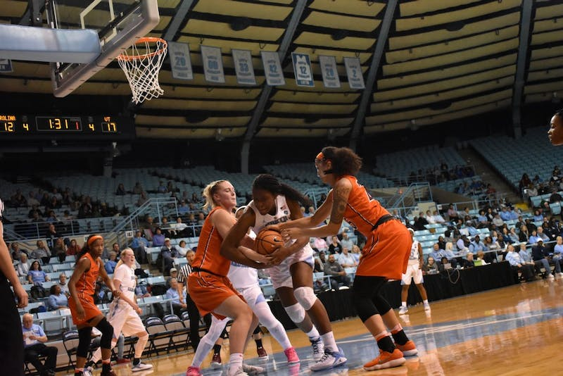 UNC center Janelle Bailey fends off two of her Virginia Tech opponents.