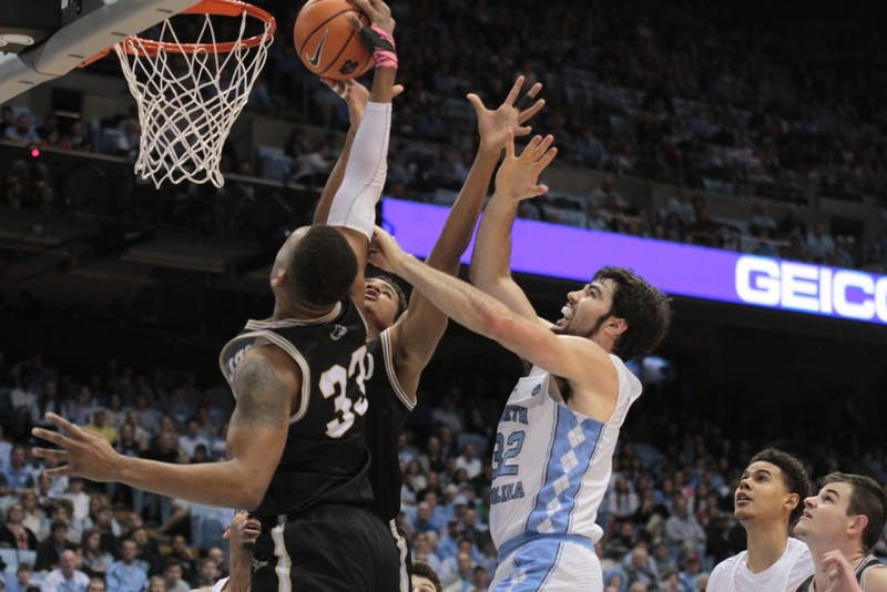Wofford forward Cameron Jackson (33) grabs a rebound over North Carolina forward Luke Maye (32) during a Dec. 20 game in the Smith Center.