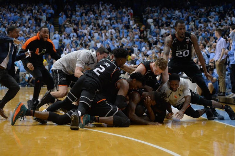 The Miami Hurricanes dogpile Ja'Quan Newton, who hit a buzzer-beating 3-pointer to beat UNC on Tuesday night in the Smith Center.