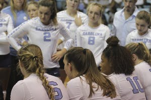 The UNC volleyball team gathers during a timeout on Friday night in Carmichael Arena.