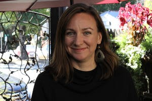 Owner of Carrburritos, Rae Fairbanks Mosher, stops and smiles out on the patio of her restaurant.