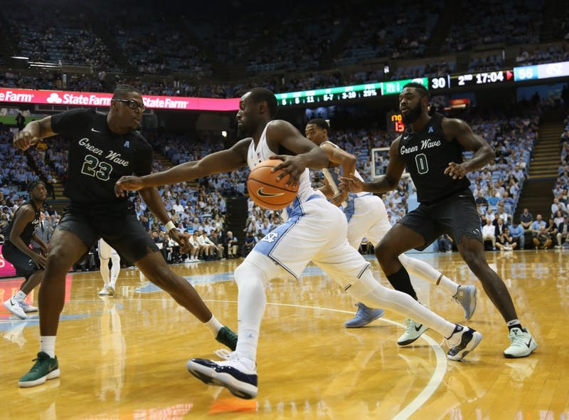 Forward Theo Pinson (1) drives past two Tulane defenders on Dec. 3 in the Smith Center.