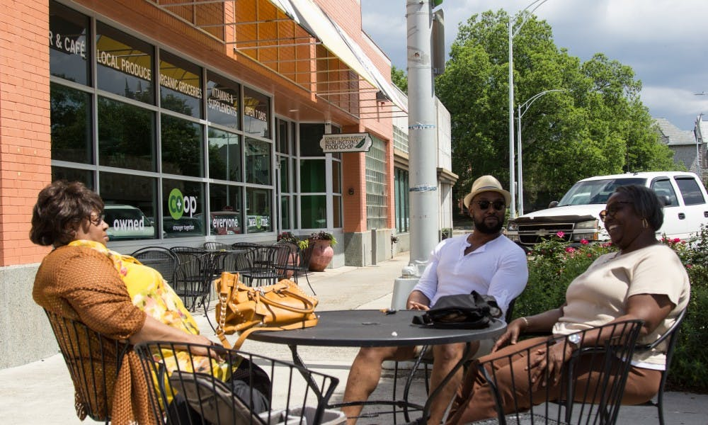From left, Linda Shanks, Greg Sellars and Ralphine Noble sit outside of the Burlington Food Co-Op after walking through the store, which on May 27 will be officially closing, May 23.