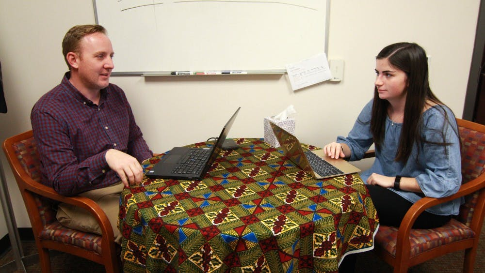 Professor Sandy Marshall works with sophomore Nicole Plante on her Lumen project regarding refugee families. [Abby Gibbs]