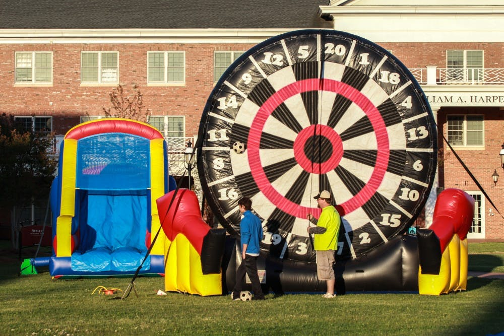 Inflatable games and activities are set up in front of Harper Hall during the Colonnades carnival on Thursday April 19. [Abby Gibbs]