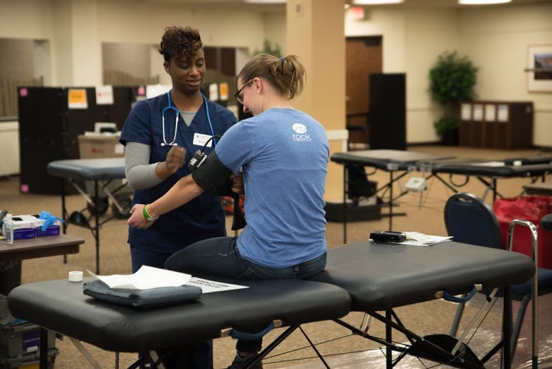 GVL / Luke Holmes - Erica helps get a student ready to draw blood. The blood drive was held by the American Red Cross in the Grand River Room Wednesday, Mar. 30, 2016