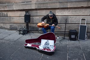 A man plays the guitar on his lap while sitting on the streets of Scotland. He was just one street musician music columnist Hannah Reed stumbled across while in Scotland.