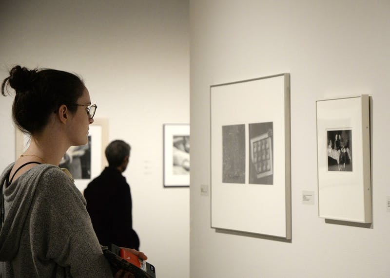 Sophomore Annie Conyngham looks at the photos from A Shared Gallery exhibit. The photography exhibit took place Tuesday at the Grunwald Gallery of Art.