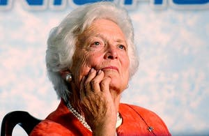 In a March 2005 file image, Former first lady Barbara Bush listens to her son, former president George W. Bush, speak during a stop in March 2005 at the Lake Nona YMCA Family Center in Orlando, Florida. Barbara Bush died April 17, 2018, in Houston, Texas.