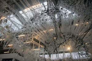 """""""Amatria"""" is a luminous and interactive sculptural landscape located in the atrium of Luddy Hall. The sculpture is comprised of 3D-printed formations and mesh-like canopies filled with pulsing mechanisms."""