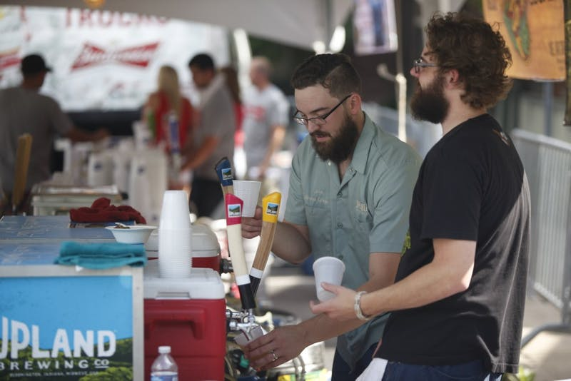 "Joe Tarnow and Carson ""M,"" part of the Upland Brewing Co. ""Brew Crew,"" pour beer for patrons June 20, 2015, at Taste of Bloomington. Upland will be releasing three new spring sours on Wednesday."