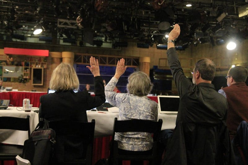 Faculty members raise their hand in agreement with a proposed new lecturer rank during the Bloomington Faculty Council meeting. The March 27 meeting was moved from its original location in Franklin Hall to Studio 6 in the Radio and Television Building.