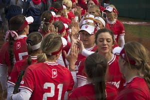 Josie Wood, center, high fives with teammates. The Hoosier's won 8-4 against University of Illinois-Chicago on Sunday, March 18.