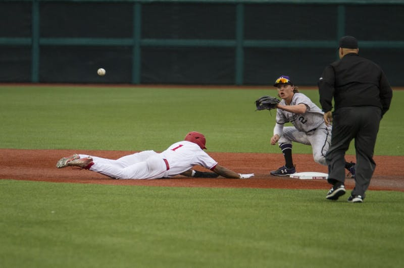 Sophomore infielder Jeremy Houston dives back to second to be safe from the umpire calling him out. IU won against Northwestern in both games, 12-0 and 6-3 on Friday.
