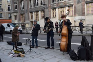 Three men play instruments on the streets of Paris as a woman dances along. Music columnist Hannah Reed said she was excited to explore the street music of Paris.