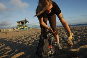 Sara Bayles collects garbage near lifeguard tower number 28 as part of a 365-day project of documenting trash she's gathered Sept. 2, 2010, in Santa Monica, California. By accident in Japan in 2016, scientists discovered an enzyme that consumes plastic.
