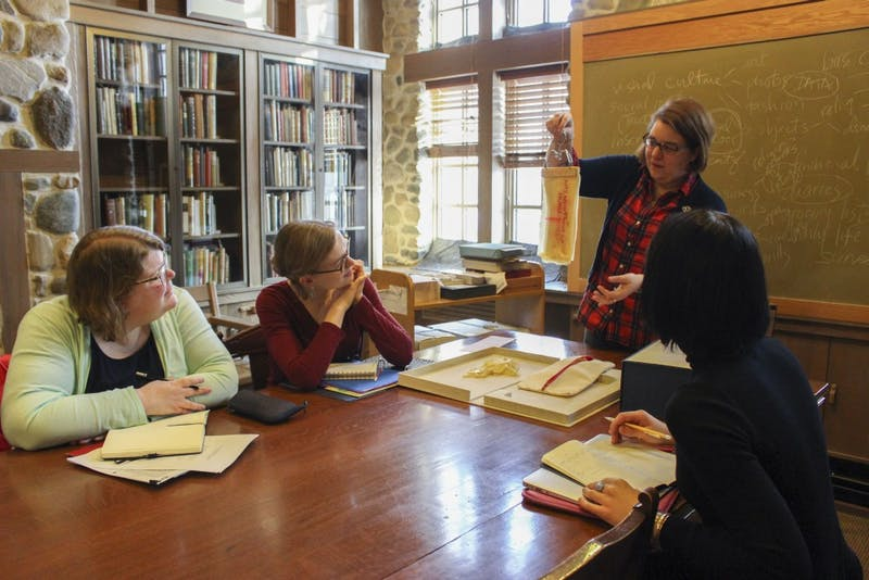 """Rebecca Baumann holds up a piece of latex with words printed on it from the book """"Lay Text."""" Seeing and discussing different types of books is part of the class called Z681:The Book 1450 to the Present ,which is taught at the Lilly Library."""