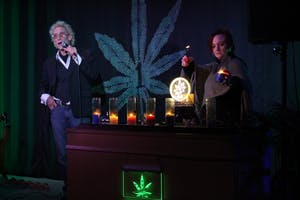 Bill Levin talks about how the candles represent the seven focus areas as a member of the First Church of Cannabis, Roo Gelarden, lights the candles. The candles represent the following: live, love, laugh, create, grow and teach.