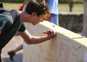 Freshman Nick Broderick signs the Wall of Prejudice during Pi Lambda Phi's Elimination of Prejudice Week event Wednesday afternoon in front of the gates of the Arboretum on Tenth Street and Fee Lane. The event is a part of Pilam's Week of Philanthropy and aims to bring hope and draw attention to prejudice on campus.