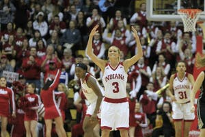 Senior guard Tyra Buss encourages the crowd to cheer after IU shoots a 3-pointer. Buss contributed 24 points to the overall score of 73, beating Purdue's 51points.