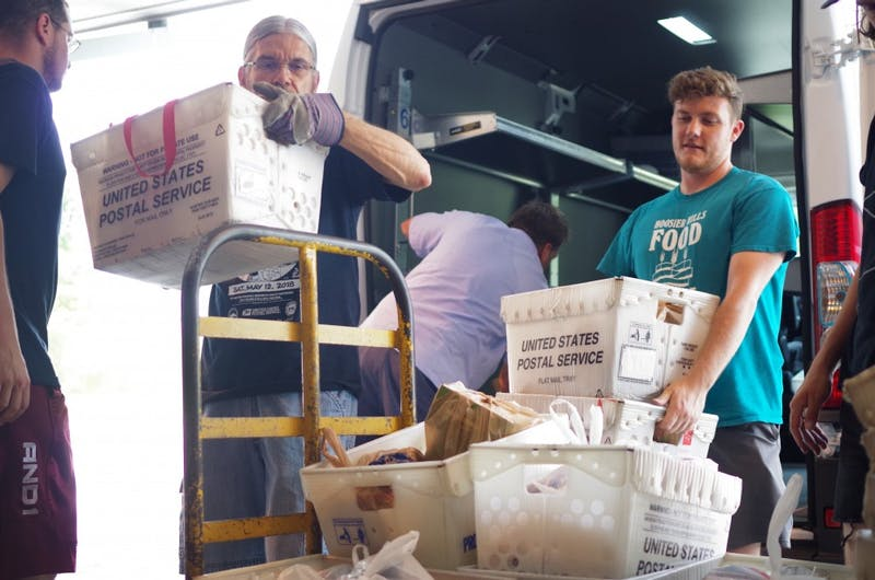 Dan Morelli, left, and Brandon Bartley, right, unload a U.S. Postal Service van during the Stamp Out Hunger food drive May 12.