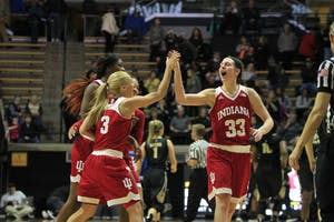 Seniors Tyra Buss and Amanda Cahill high-five after the game against Purdue. Together, the two seniors scored 29 points, adding to the winning score of 52-44 against Purdue on Monday, Feb. 12, in West Lafayette, Indiana. The two will play their final regular season home game against Nebraska on Saturday.