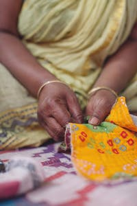 A woman from Sari Bari, an organization that helps women in India leave the sex trafficking by training them as artisans, repurposes an old sari, which is an Indian female garment. Photographs from photographers Frank and Sarah Schweikhardt, who visited Sari Bari in Calcutta, India, will be displayed at Gather until Jan. 31.