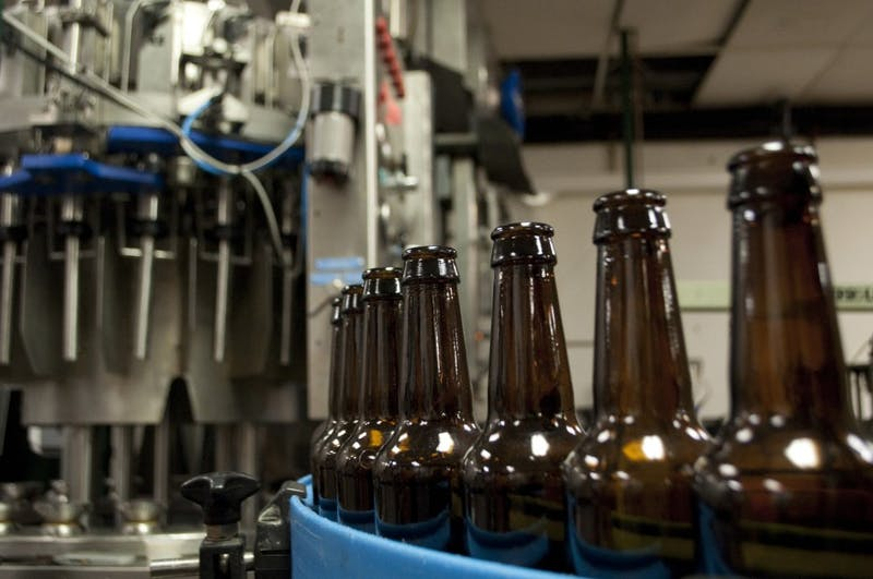Upland Brewery beer bottles are lined up in a row on a machine. The brewery will be releasing new beers for their 20th anniversary.